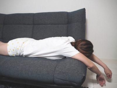 ソファでへばっている女性