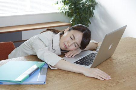 疲れて机に突っ伏している女性