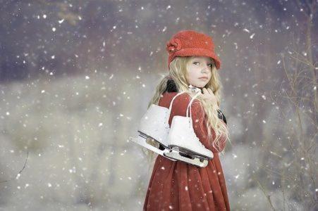 スケート靴を持った雪の中の少女